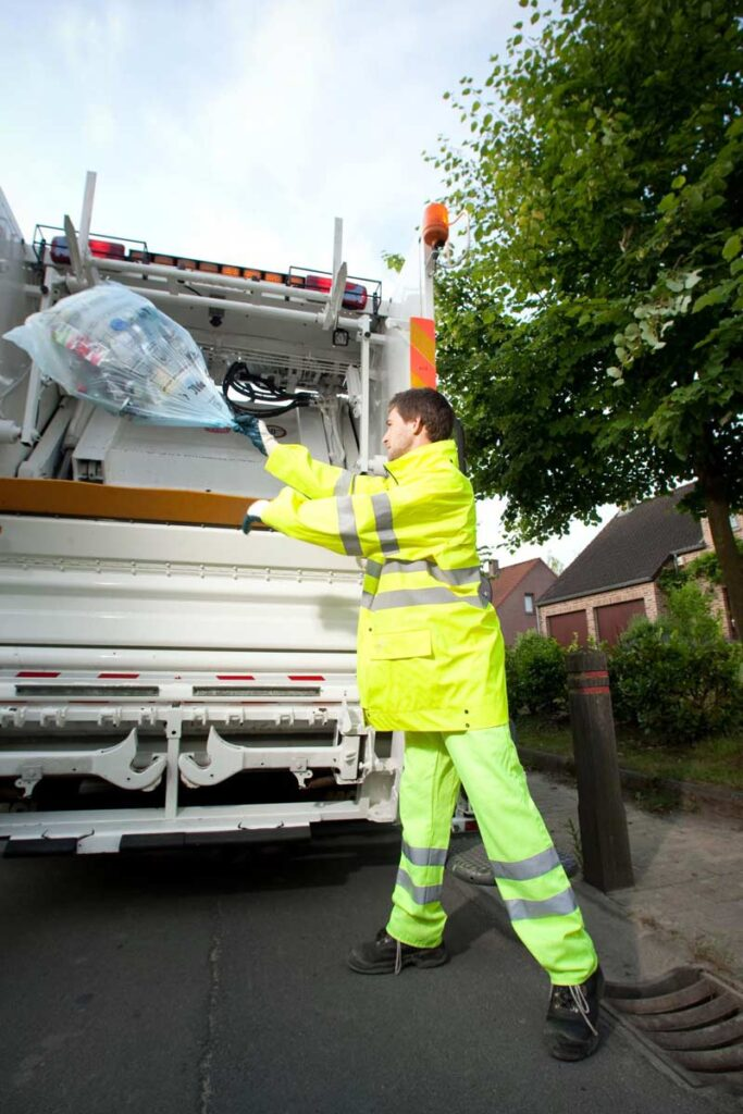 An operative throwing collected recycling into a collection vehicle